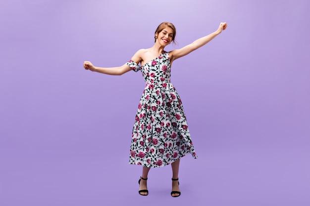 Chica alegre en vestido estampado floral baila sobre fondo morado. hermosa mujer joven hermosa en traje de verano de moda y tacones negros tiene ventilador.