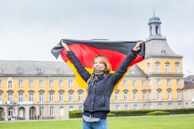 Chica alemana con bandera frente a la universidad de bonn