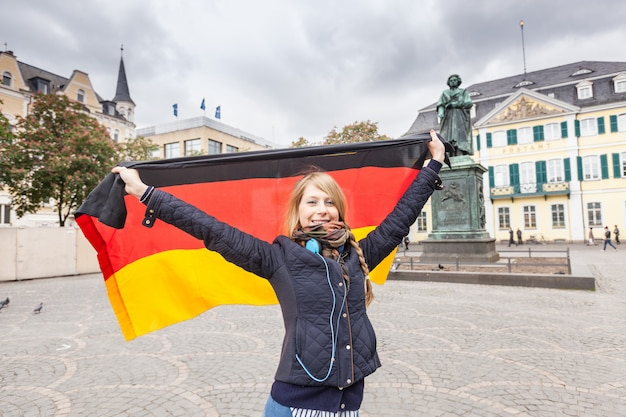 Chica alemana con bandera en la plaza principal de bonn