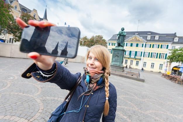 Chica alemana tomando selfie en la plaza principal de bonn