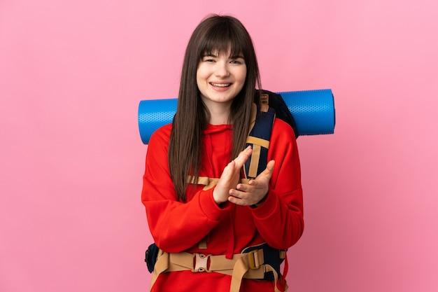 Chica alpinista con una gran mochila aislada en rosa aplaudiendo