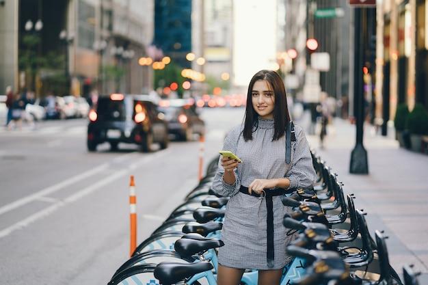 Chica alquilando una bicicleta de ciudad en un puesto de bicicletas.