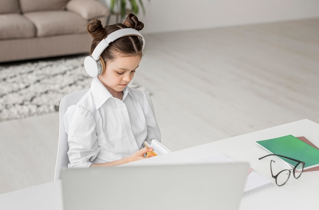 Chica de alto ángulo escuchando a su maestra a través de auriculares