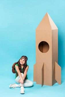 Chica de alto ángulo con juguete de avión de dibujos animados