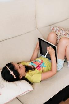 Chica de alto ángulo con tableta sentado en el sofá