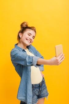 Chica de alto ángulo tomando selfie