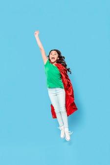 Chica de alto ángulo con traje de héroe volando