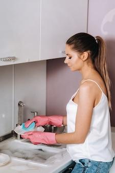 Chica ama de casa en guantes rosados lava los platos a mano en el fregadero con detergente