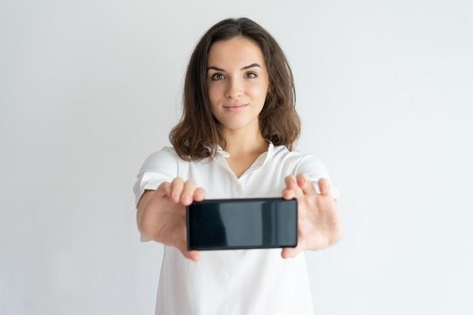 Chica amable positiva presentando nuevo servicio móvil o aplicación en la pantalla del teléfono móvil.