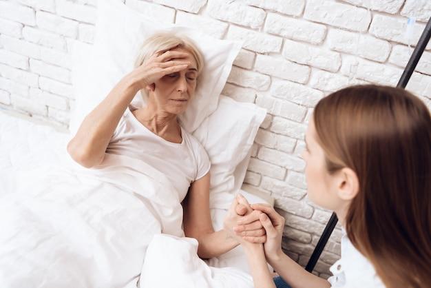 Chica está amamantando a una anciana en casa