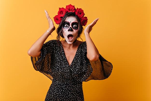 Chica de américa latina con maquillaje de calavera reacciona emocionalmente y posa para retrato en pared naranja