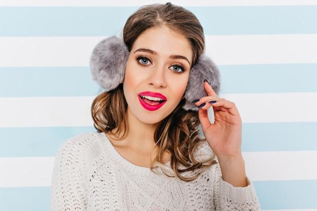 Chica amigable y atractiva con un hermoso maquillaje que enfatiza los ojos azules luciendo lindos con una sonrisa suave.