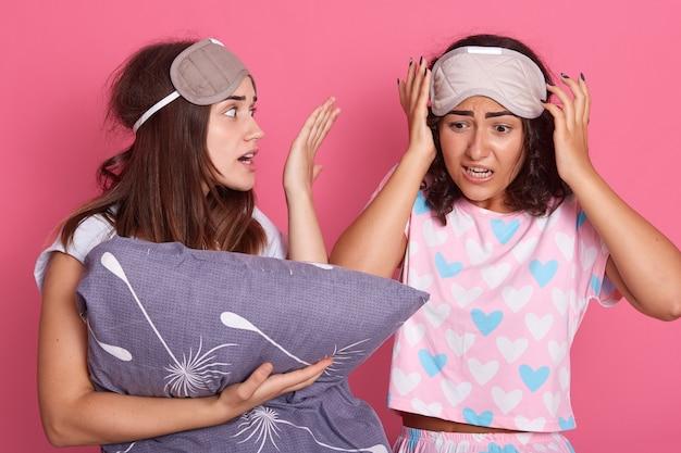 Chica de amigos molestos en traje de noche para una fiesta de pijamas sobre fondo rosa