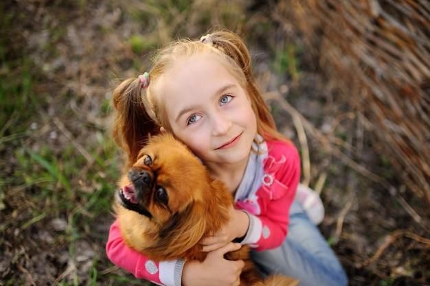 Chica con amigos de perro en el césped en el parque