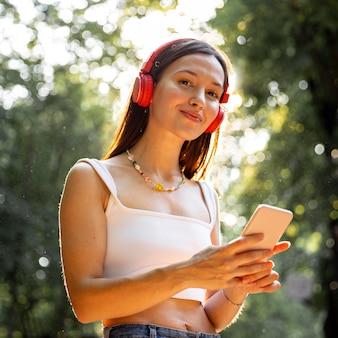 Chica de ángulo bajo con auriculares