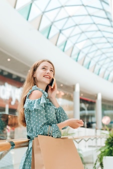 Chica de ángulo bajo con bolsas de compras en el centro comercial