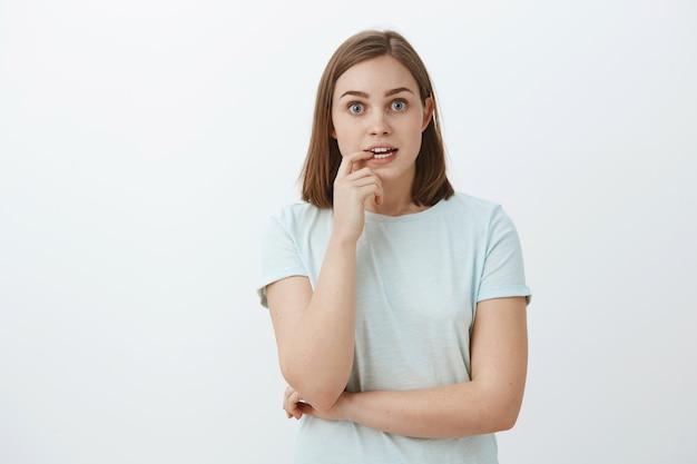 Chica ansiosa por conocer el final de la historia muriendo de emoción e interés. retrato de curiosa mujer de buen aspecto, entusiasta y emocionada, ventilador de la serie de televisión mordiendo la uña y mirando enfocado