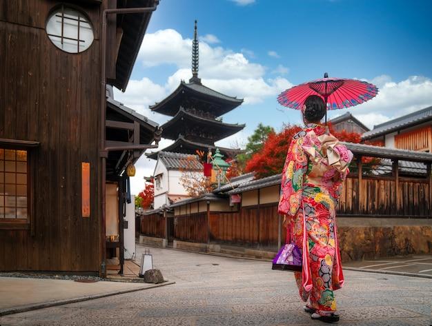 Chica apanesa caminar en el antiguo mercado de kyoto y la pagoda boscosa de yasaka