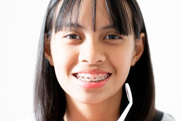Chica de aparatos dentales sonriendo y mirando a la cámara, se siente feliz y tiene una buena actitud con el dentista