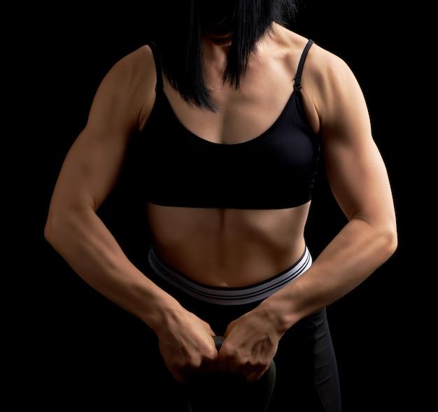 Chica de apariencia atlética sostiene una pesa de hierro frente a ella