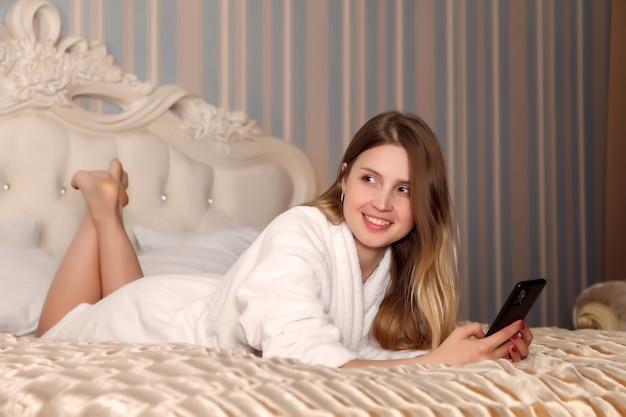 Chica de apariencia eslava en bata blanca con teléfono en la cama en la habitación del hotel
