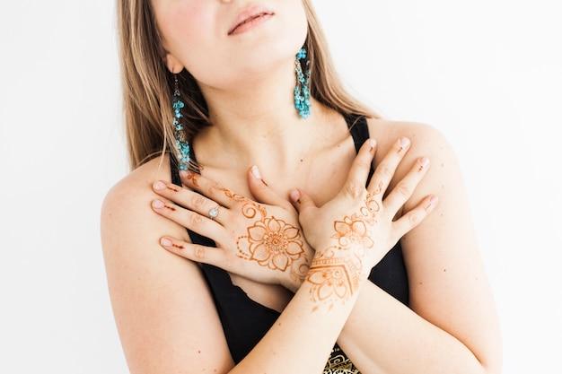 Chica de apariencia europea, henna dibujando en las manos, mahendi, chica en ropa ligera, yoga, desarrollo espiritual