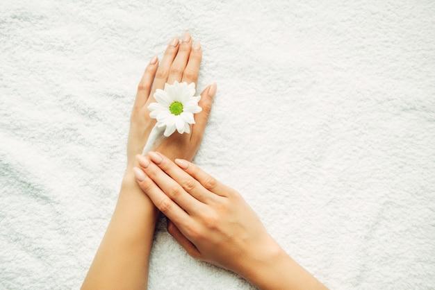 Chica aplica crema natural en primer plano de la mano. vista superior de manos femeninas