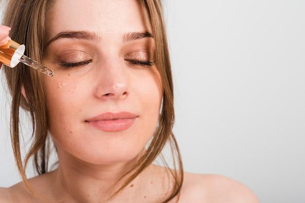 Chica aplicándose productos cosméticos