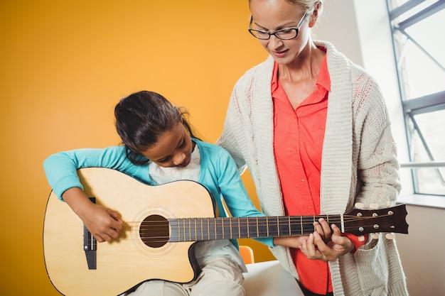 Chica aprendiendo a tocar la guitarra