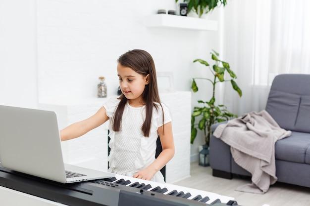 Chica aprendiendo a tocar el piano en casa siguiendo un tutorial en línea