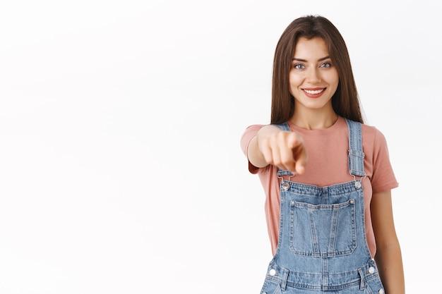 Chica apuntando hacia ti como haciendo una elección, reúne al equipo. atractiva cámara indicadora femenina linda confiada y motivada con expresión satisfecha y segura de sí misma, fondo blanco de pie