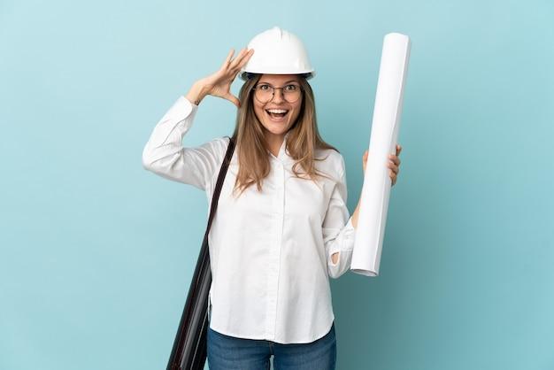 Chica de arquitecto eslovaco sosteniendo planos aislados en la pared azul con expresión de sorpresa