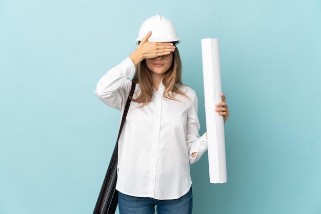 Chica de arquitecto eslovaco sosteniendo planos aislados en la pared azul que cubre los ojos con las manos. no quiero ver algo