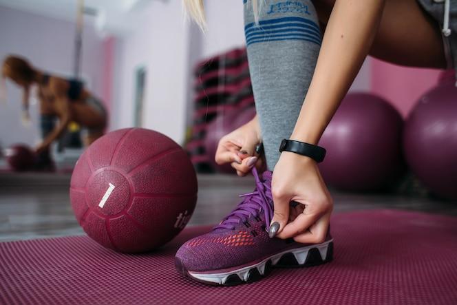 Chica arregla sus snickers violetas antes del entrenamiento en un gimnasio