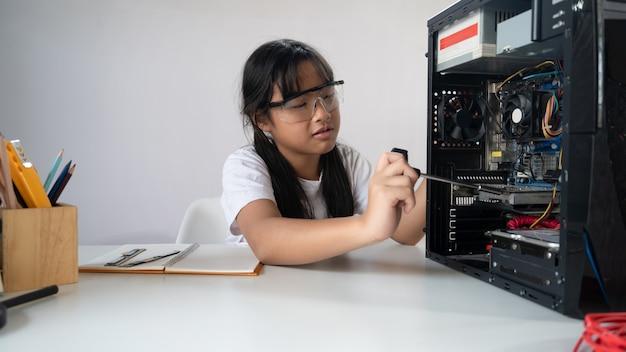 Chica está arreglando hardware de computadora en el moderno escritorio blanco.