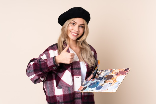 Chica artista adolescente sosteniendo una paleta en la pared azul dando un gesto de pulgares arriba