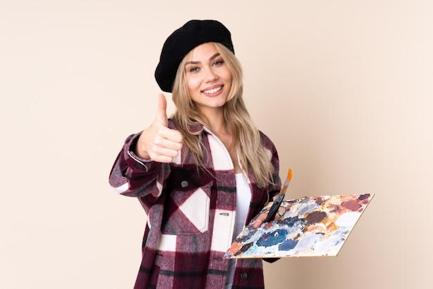 Chica artista adolescente sosteniendo una paleta en la pared azul con los pulgares hacia arriba porque algo bueno ha sucedido