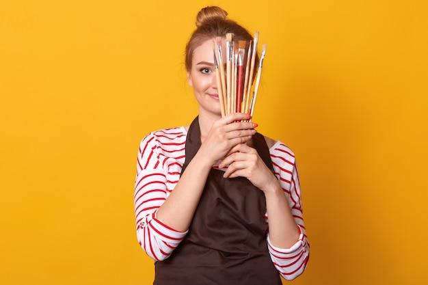 Chica artista sostiene pinceles en las manos y se esconde detrás de ella, la dama viste una camisa casual de rayas y un delantal marrón, una mujer rubia con racimo