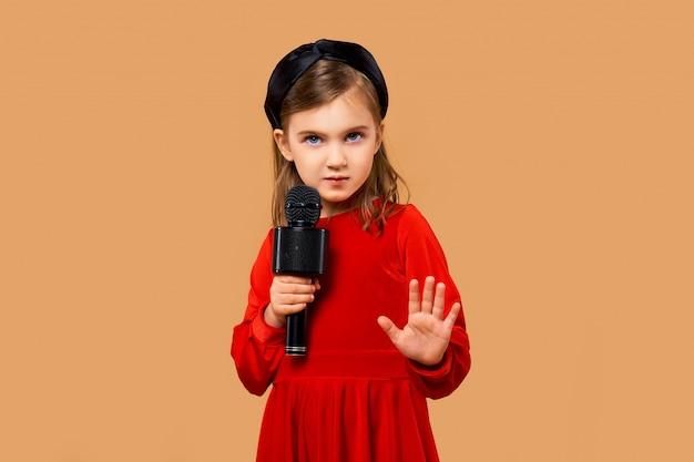 Chica artística en vestido rojo cantando en micrófono de karaoke