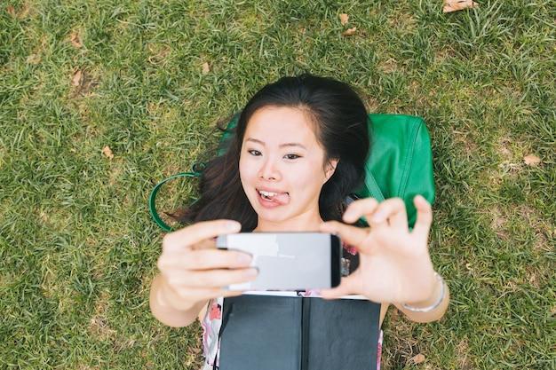 Chica asiática acostada en la hierba y tomando selfie