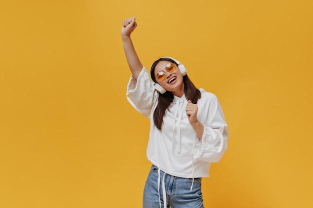 Chica asiática adolescente activa en jeans y sudadera con capucha blanca canta, levanta la mano y escucha música en grandes auriculares en una pared naranja aislada