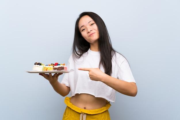 Chica asiática adolescente sosteniendo muchos mini pasteles diferentes y apuntando