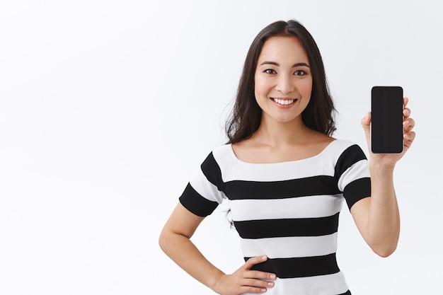 Una chica asiática amable, tierna y femenina con una camiseta a rayas recomienda descargar la aplicación, sosteniendo un teléfono inteligente, mostrando la pantalla del móvil en blanco, sonriendo con alegría, una mano en la cadera, fondo blanco