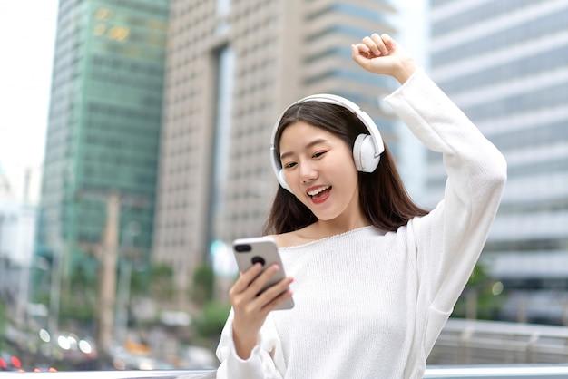 Chica asiática con auriculares escuchando música en línea desde un teléfono inteligente