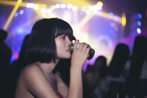 Chica asiática bebiendo cerveza en un bar