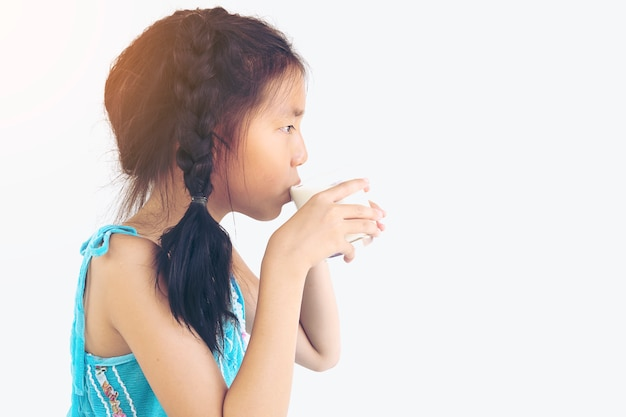 Chica asiática está bebiendo un vaso de leche sobre fondo blanco