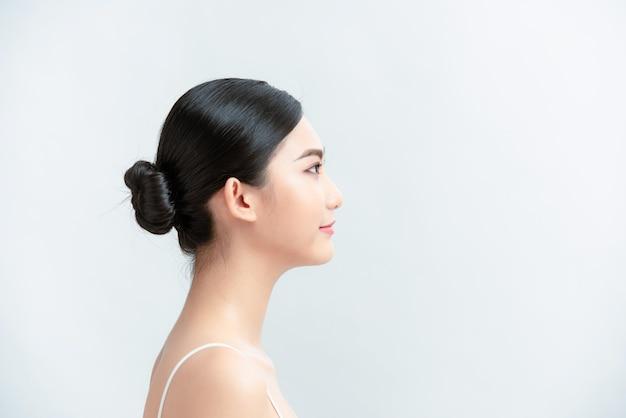 Chica asiática belleza cara cuidado de la piel y bienestar de la salud en la pared blanca
