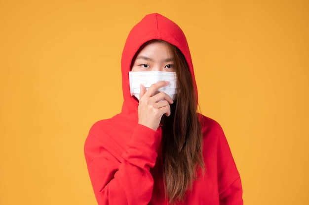 Chica asiática con capucha con mascarilla protectora para protegerse durante el brote de coronavirus covid19 de cuarentena sobre fondo amarillo, proteger la propagación covid-19