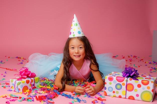 Chica asiática celebra cumpleaños, confeti en rosa