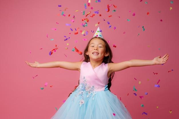 Chica asiática celebra cumpleaños golpes atrapa confeti en rosa